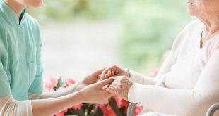 enfermeiro segurando mão de idosa doente, na humanização em saúde