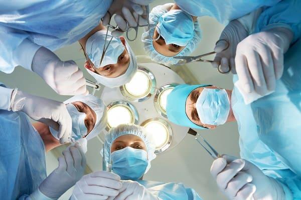 médicos cirurgiões com sua aparelhagem para evitar lesão nervosa pós-operatória