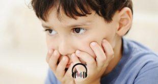 criança com TDAH com as mãos na boca