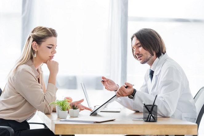 médico orientando mulher com infecção do trato urinário recorrente