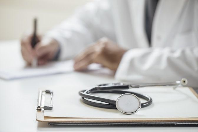 mãos de médico preenchendo prescrição para paciente com osteoartrite de mãos