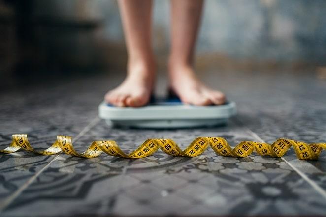 pés de pessoa com obesidade em cima de de balança com fita métrica na frente