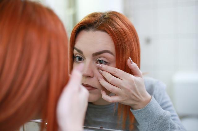 mulher colocando lentes de contato no espelho