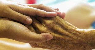 enfermeiro segurando mão de paciente em fase final de vida, pensando no cuidado após óbito