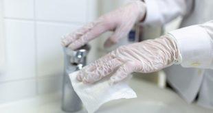 enfermeira com luvas desinfeta objeto em sala hospitalar por contato de paciente com coronavírus