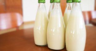 vidros de leite em cima de uma mesa