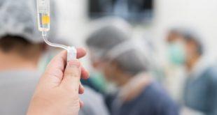 mão de enfermeiro regulando fluidos intravenosos em cirurgia com uso do ácido tranexâmico