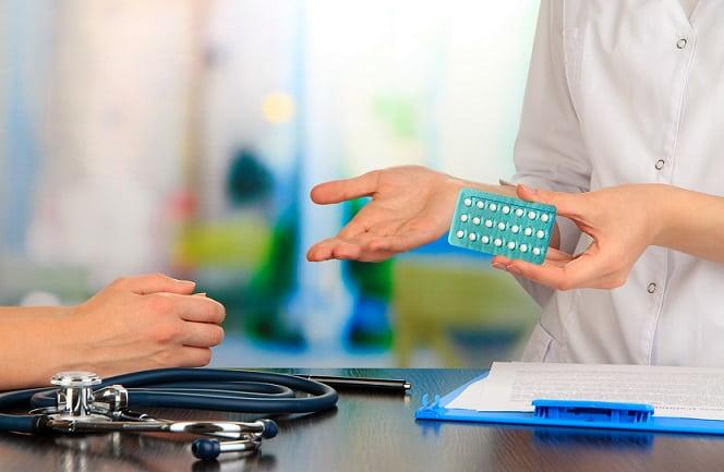 médico falando sobre contraceptivo, com uma cartela na mão, e sua relação com a leucemia