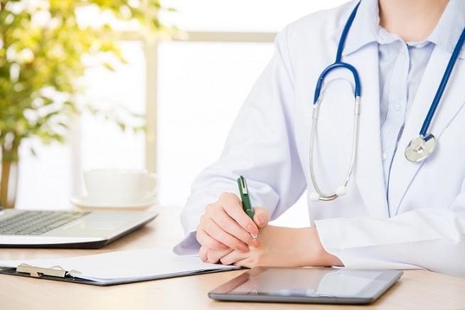 médico escrevendo em prontuário com tablet aberto na mesa