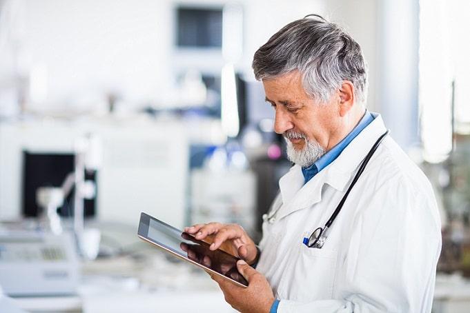 médico olhando o whitebook no tablet em hospital para ver novidades de coronavírus covid-19