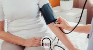 paciente com idosa ao lado de enfermeiro aferindo sua pressão; paciente tem hipertensão e risco de coronavírus