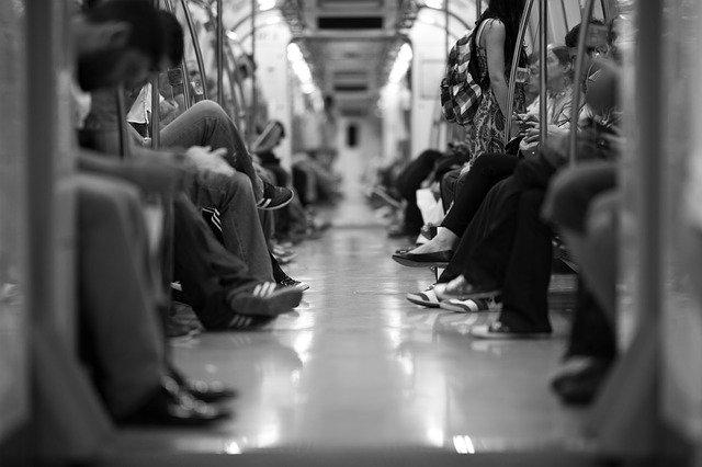pés de pessoas sentadas em metrô