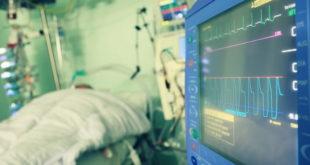 monitor de UTI em foco, com paciente com coronavírus ao fundo
