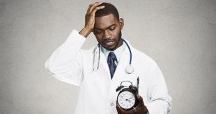 médico com uma mão na cabeça e um relógio na outra, sofrendo burnout