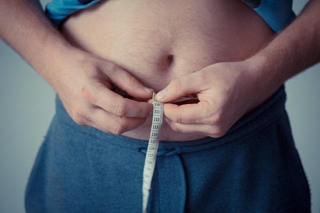 homem com obesidade, fator de risco para coronavírus, medindo circunferência, com a barriga e fita métrica em foco
