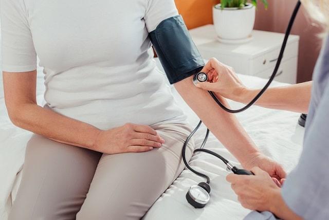 médico aferindo pressão de mulher com hipertensão arterial