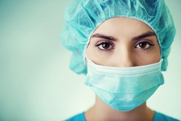 mulher com máscara e touca em residência em saúde no combate ao coronavírus
