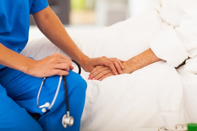 profissional da enfermagem de mão dada com paciente internada, mãos em foco