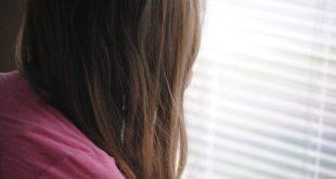 menina de costas, olhado para janela fechada durante quarentena do coronavírus