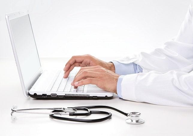médico escrevendo em computador para uso de telemedicina