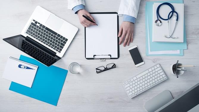 mesa com computador, estetoscópio, bloco de folhas e óculos de médico em quarentena
