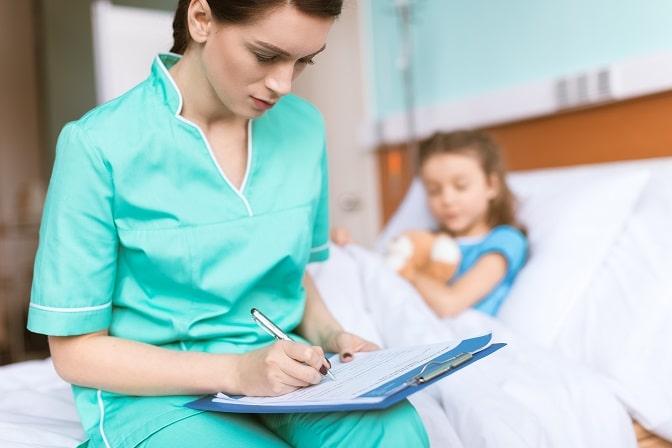 enfermeira anotando recomendações com criança com câncer ao fundo, durante pandemia de covid-19