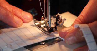 mãos de costureira fazendo máscara caseira em máquina de costura para Covid-19