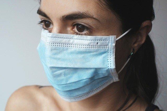 mulher usando máscara cirúrgica em distanciamento social por coronavírus
