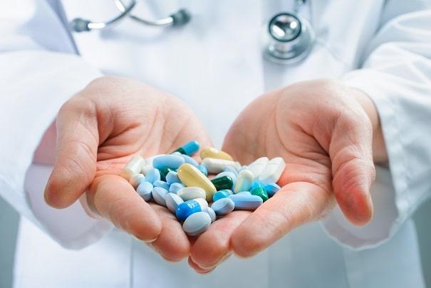 mãos de médico segurando comprimidos de antibióticos