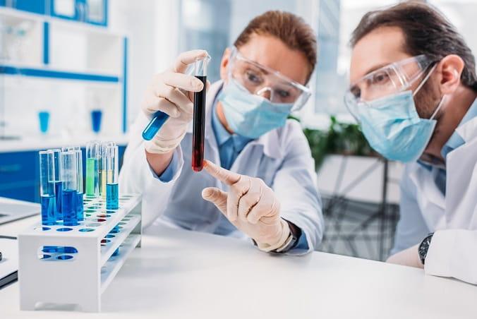 médicos laboratoristas avaliando tubo com sangue em point-of-care testing