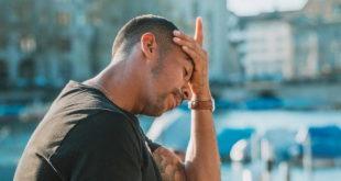 homem com a mão na cabeça por transtorno de estresse relacionado à covid-19