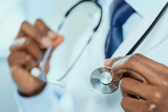 médico segurando estetoscópio, mãos em foco, para tratar rosácea