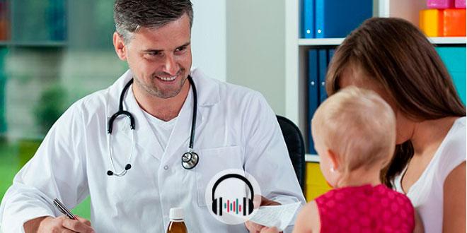 médico sorrindo para criança no colo da mãe durante consulta devido ao coronavírus na pediatria