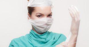 Médica se preparar para o atendimento de pacientes com suspeita de Covid-19, verificando seus equipamentos de proteção.