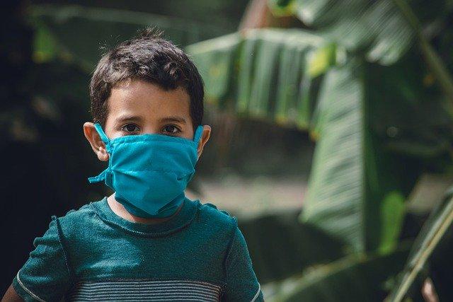 menino com covid-19 usando máscara
