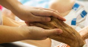 enfermeiro segurando mão de paciente idosa, usando espiritualidade na enfermagem