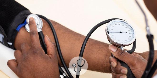 mão de médico aferindo pressão de paciente com hipotensão ortostática