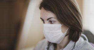 mulher usando máscara por conta da Covid-19