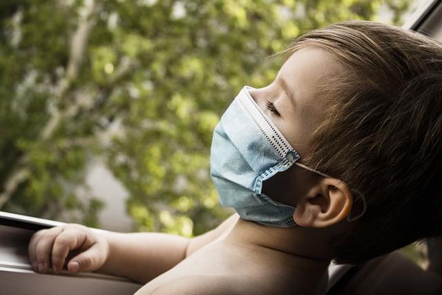 criança com covid-19 usando máscara deitada no carro