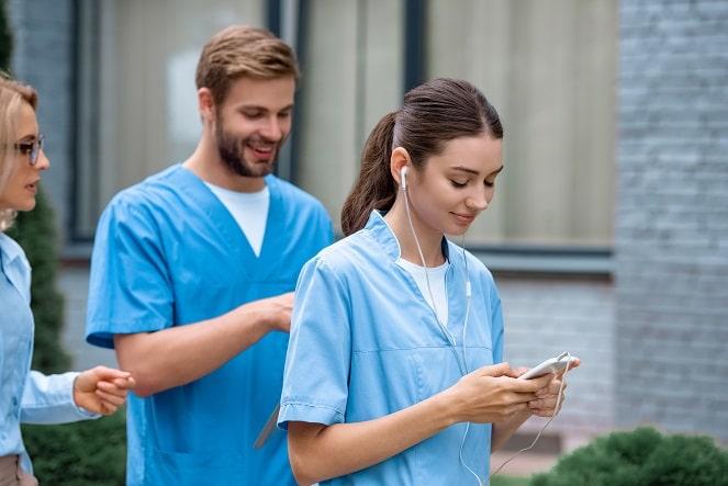 enfermeira usando celular para consultar o nursebook em hospital