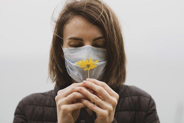 Mulher verifica se sua capacidade de sentir cheiros foi afetada pelo diagnóstico positivo de Covid-19.