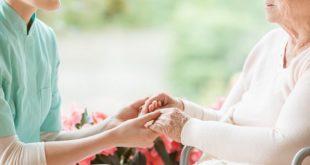 enfermeiro segurando as mãos de paciente idosa após usar o nursebook