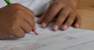criança escrevendo em caderno na escola que reabriu após Covid-19
