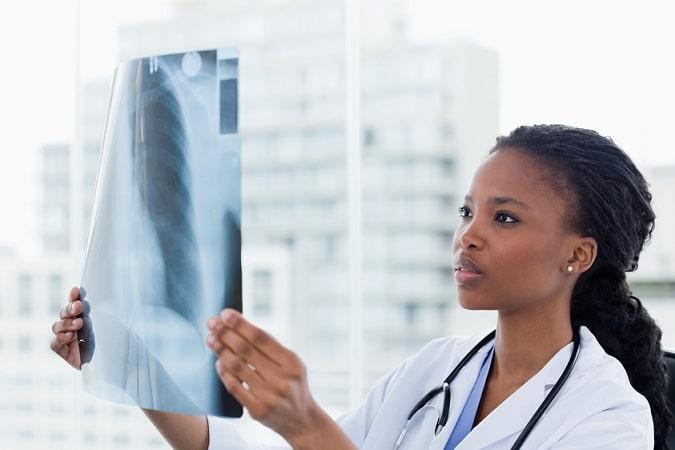 médica comparando exame de imagem com atlas de radiologia do whitebook