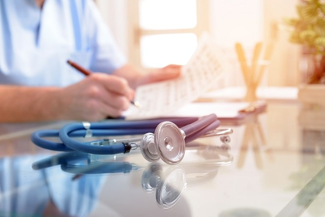 enfermeiro escrevendo em prontuário de paciente com coronavírus