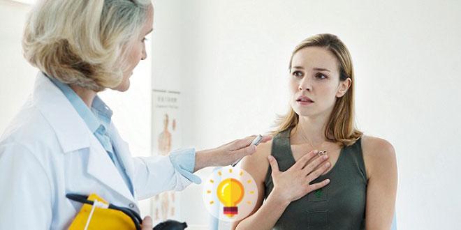mulher com a mão no peito em consulta com médica