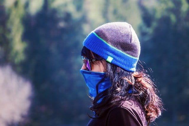 Mulher usa máscara contra a epidemia de Covid-19 em dia de baixa temperatura.