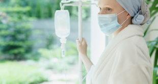 mulher com câncer, usando máscara e lenço, na janela, esperando tratamento que consta no nursebook