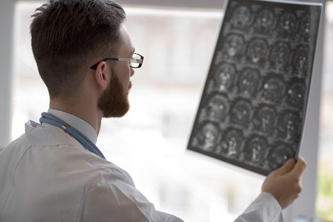 médico avaliando imagem com atlas de radiologia do whitebook