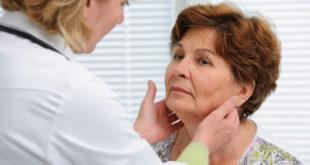 médica avaliando tireoide de paciente com possível câncer